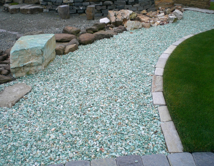 Oro Verde crushed stone rock in backyard with boulders next to grass lawn