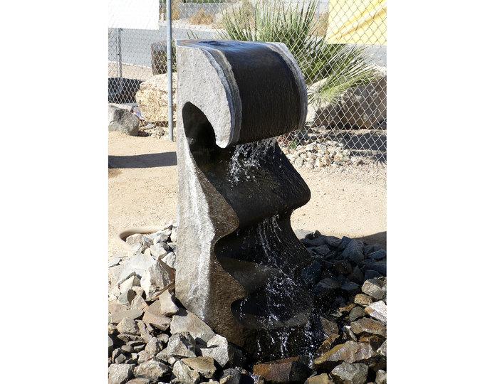 Basalt wave stone fountain installed around pebble in water pond 2