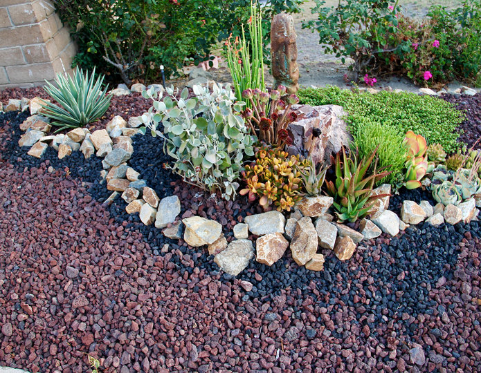 Red lava crushed stone rock installed in front yard landscaping project