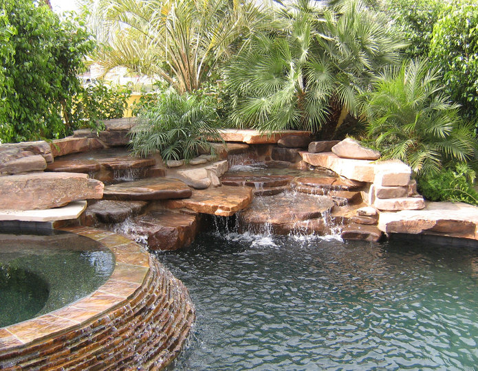 Coco Flats Premium Slab landscape boulders installed around pool and waterfall