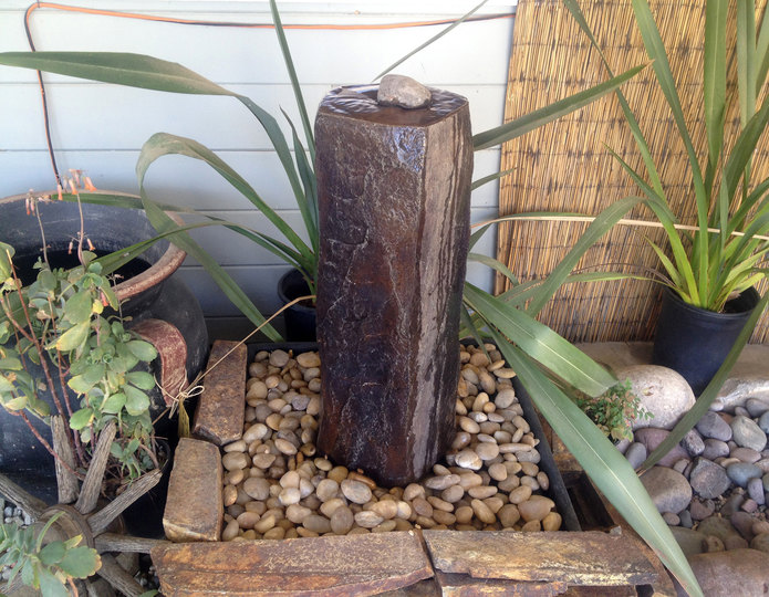 Faux Basalt Column Stone Fountain installed over pebbles