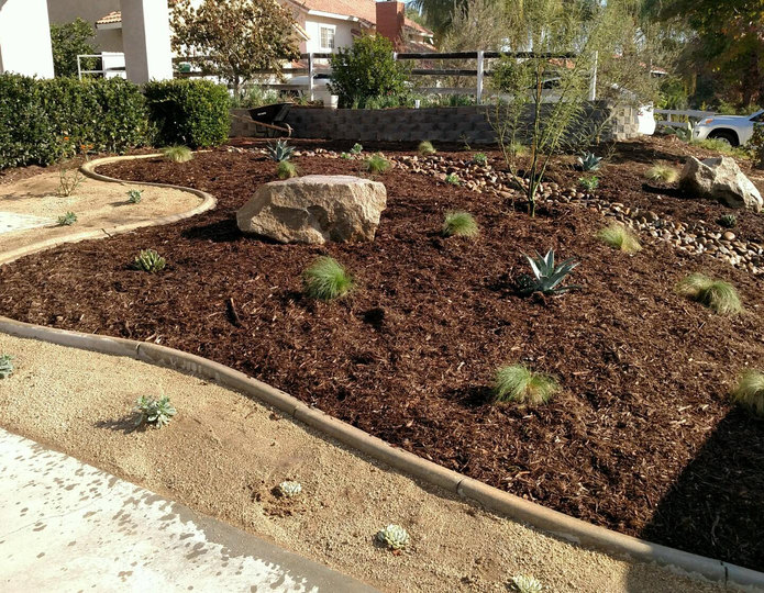 Supreme Walk-On Bark landscape mulch groundcover installed in front yard with boulders and decomposed granite