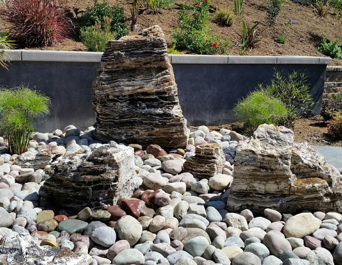 Black canyon onyx boulder fountains on cobblestones in backyard