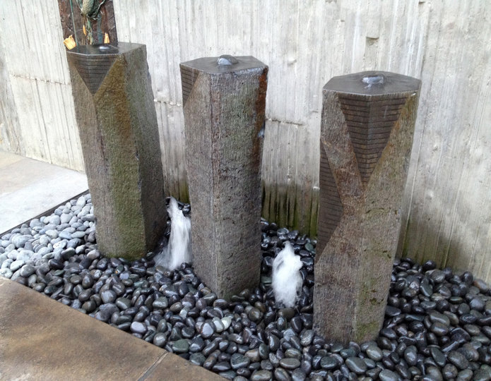 Three sisters custom stone fountain installed over mexican beach pebble
