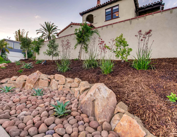 Supreme Walk-On Bark landscape mulch groundcover installed in backyard with boulders and cobblestones.