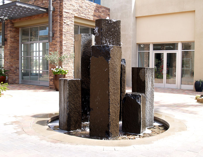 Bronze basalt stone fountain collection installed in front of commercial building