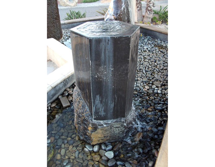 Dark Marble Hexagon Stone fountain installed in water pond with pebbles