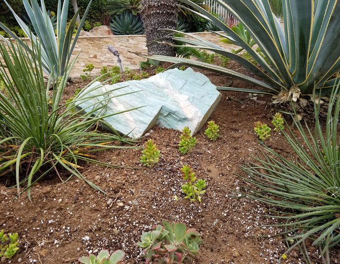 Turquoise landscape boulder in garden with succulents and plants