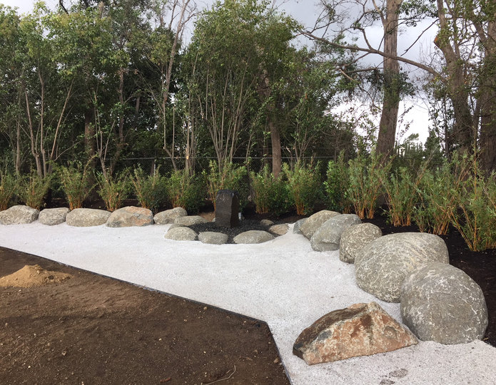 Smokey white ice decomposed granite fines installed in backyard with boulders 2