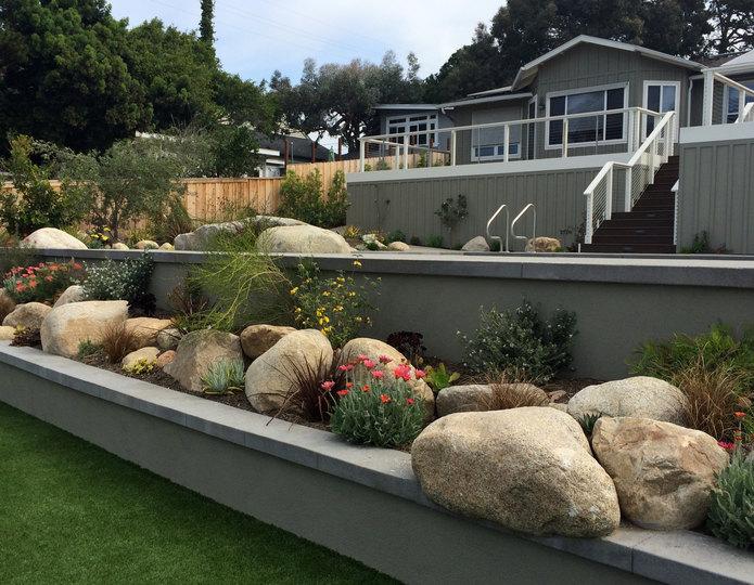 Desert Sand landscape boulder in flower garden by grass lawn