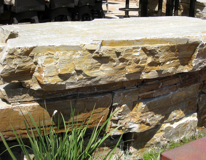 Gold Quartzite landscape rock boulders installed in garden