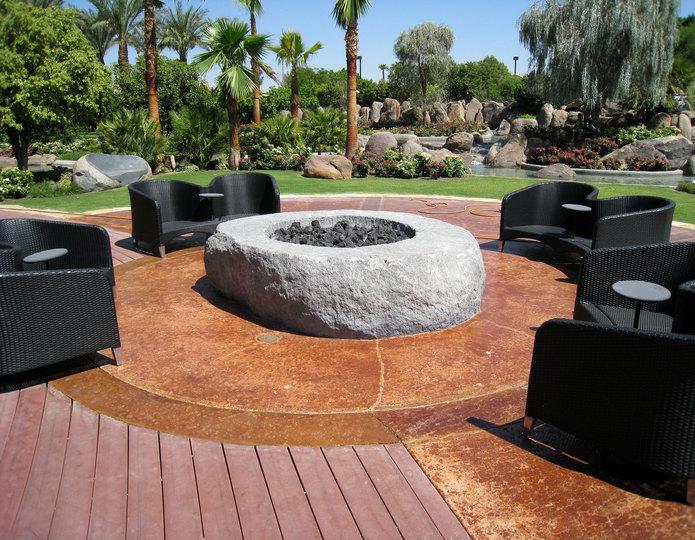 Custom granite stone fire pit installed in backyard patio