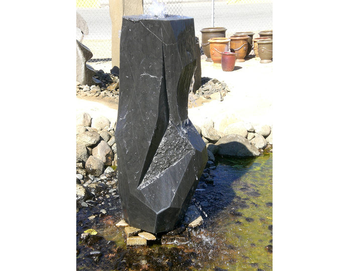 Mizubachi polished black custom stone fountain installed in rock pond at rock yard