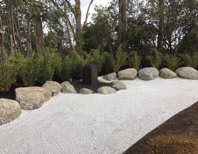 Smokey white ice decomposed granite fines installed in backyard with boulders