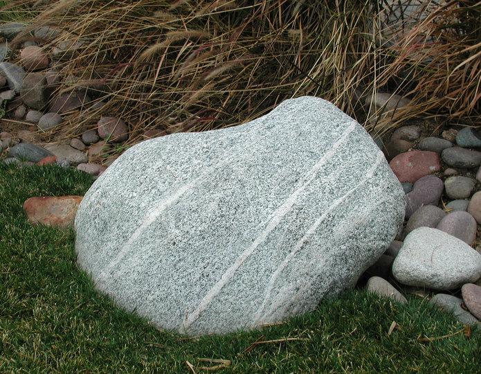 Desert Marble landscape boulder installed on grass by garden